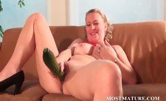 Mature blonde masturbates with a cucumber